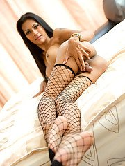 Sexy Thai shemale Rose jerking off big dick in black fishnet stockings