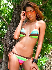 Pretty Thai shemale Moo goes outsise to strip naked and flash big tits