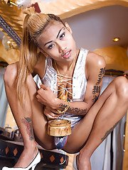 Tattooed Thai tranny posing in high heels and masturbating with toys