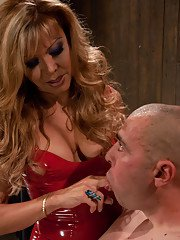 Mature blonde shemale Johanna B dominating a man in latex