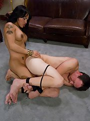 Tattooed brunette shemale Foxxy sitting her fat ass down on a hard dick