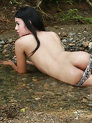 Cute Ladyboy Shane removes her bikini to flash her privates outdoors in a small river