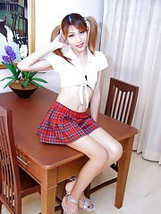 Cute Asian schoolgirl tranny in pigtails and pleated skirt flashes big dick