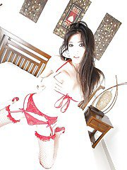 Brunette Asian shemale May A showcasing her big boobs in red stockings