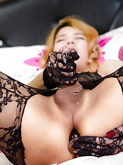 Beautiful blonde Asian tranny Lisha posing on her bed in full body lingerie
