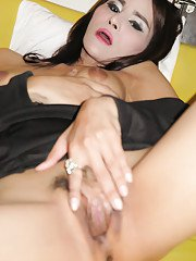 Small tit brunette Asian tranny Angie spreading her pussy on a bed