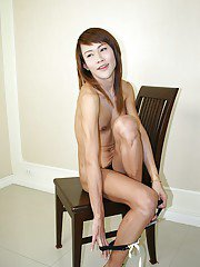 Thin Asian ladyboy June slips out of her dress and plays with her cock