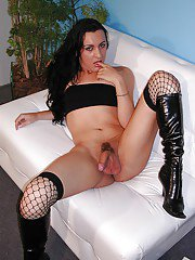Slender shemale Camila Di Paula posing solo in fishnet stockings and boots