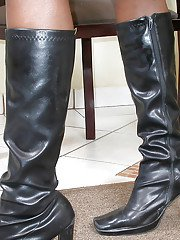 Solo ebony tranny model Domenyca Galdino posing in latex uniform and boots